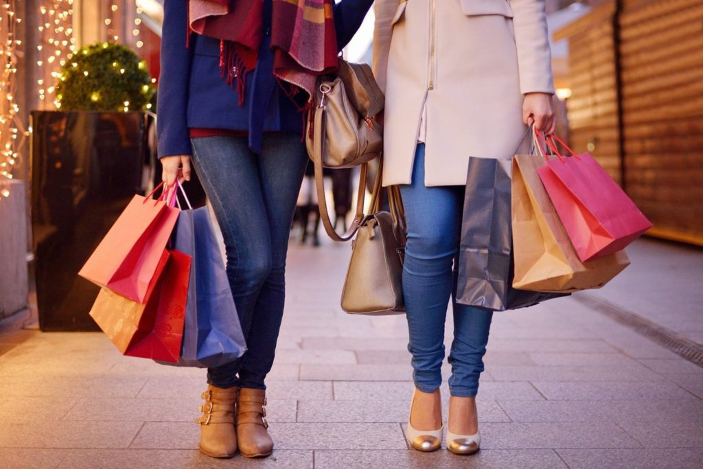 Young women shopping in the city, legs and hands close up, carrying paper bags.